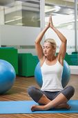 Sporty young woman with joined hands and eyes closed at fitness studio