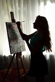 Silhouette Woman Artist Draws Paint Picture On Easel, Backlight Portrait Indoor