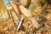stock photo of thermos  - Female hiker holding thermos outdoors in autumn forest view of legs - JPG