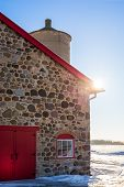 Old Stone Barn With Bright Red Door And Sunflare