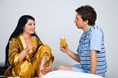 Couple With Fresh Orange Juice On Bed In Morning