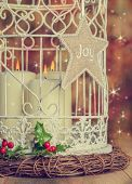 Christmas candles in birdcage with joy decoration and vintage effect - focus on joy decoration