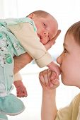 Boy Kissing A Newborn Sister's Hand