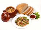 foto of pot roast  - roast with greens sauce bread and tomato in a brown clay pot - JPG