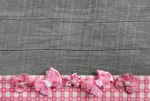 Shabby chic wooden grey background with pink ribbon on white checked frame for decoration.