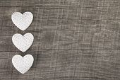 Decoration: Three white hearts on an old grey brown wooden background.