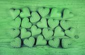 Green shabby chic or wooden country background with a collection of hearts.