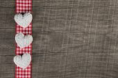 Rustic wooden background with red white checkered frame and three hearts.