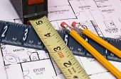Measuring Tape and Ruler with pencils on house floorplan