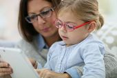 Mother and daughter with eyeglasses playing with tablet