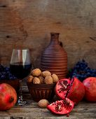 Pomegranate, Walnuts, Grapes And Wine On A Wooden Background.