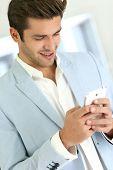 Man with blue jacket sending short message on smartphone