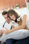 Young trendy couple having fun playing with smartphone
