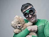 Smiling Superhero Cuddling A Teddy Bear