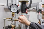 stock photo of pressure vessel  - Technician checking water pressure in apartment building - JPG