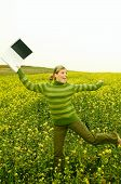 stock photo of computer-screen  - Young business woman with laptop computer on green meadow full of yellow flowers - JPG