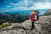 foto of mountain-climber  - Young woman mountain climber with backpack and sleeping back hiking on the rocky mountain