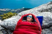 stock photo of sleeping bag  - Young woman lying in red sleeping bag on the rocky mountain - JPG