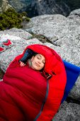 stock photo of sleeping bag  - Young woman sleeping in red sleeping bag on the rocky mountain - JPG