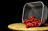 stock photo of plum tomato  - Stainless steel basket filled with plum tomatoes with rosemary sprigs on a bamboo cutting board isolated on black