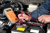 stock photo of car repair shop  - An auto mechanic uses a multimeter voltmeter to check the voltage level in a car battery - JPG