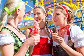 picture of national costume  - Friends visiting together Bavarian fair in national costume eating sundae ice - JPG