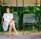 image of swingset  - Woman sitting on the swingset - JPG