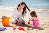 stock photo of babysitter  - Pretty young brunette and her daughter building a sand castle on the beach - JPG