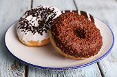 foto of donut  - Delicious donuts with icing on plate on wooden background - JPG