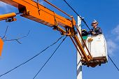 foto of pole  - Technician works in a bucket high up on a power pole.