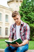 pic of sitting a bench  - Confident male student reading book while sitting on the bench and in front of university building - JPG