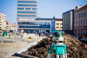foto of geodesic  - Surveying measuring equipment level transit on tripod at construction building area site - JPG
