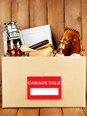 picture of yard sale  - Box of unwanted stuff ready for a garage sale on wooden background - JPG