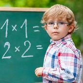 Preschool Kid Boy With Glasses At Blackboard Practicing Mathematics poster