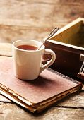 picture of old suitcase  - Old wooden suitcase with old books and tea cup on wooden background - JPG