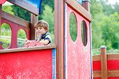 foto of imaginary  - Funny kid boy pretends driving an imaginary car on children playground outdoors - JPG
