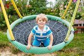 picture of swing  - Adorable toddler boy having fun chain swing on outdoor playground - JPG
