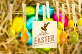 pic of egg-laying  - happy easter against easter eggs grouped together on straw - JPG