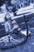 stock photo of hurt  - Young female bicyclist with hurt leg sitting on grass in the park - JPG