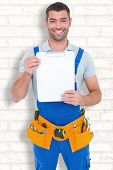 picture of clipboard  - Portrait of happy repairman showing blank clipboard against white wall - JPG