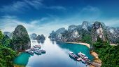 stock photo of southeast  - Tourist junks floating among limestone rocks at Ha Long Bay South China Sea Vietnam Southeast Asia
