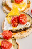 foto of aubergines  - Healthy Italian appetizer of rice cracker topped with baked egg and juicy grilled aubergine and cherry tomatoes. ** Note: Shallow depth of field - JPG