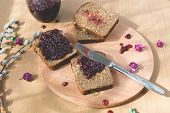 image of dry fruit  - Fresh baked homemade healthy bread with blackcurrant jam -marmalade with fresh organic fruits from garden. In rustic decoration,dried roses, silver spoon and knife, fruit jam on toasted breadon wooden table background. 