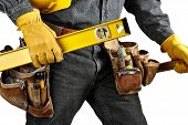 stock photo of leather tool  - Man in black denim wearing used tool belt filled with carpenter tools carrying a yellow level hardhat and hammer - JPG