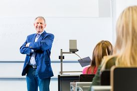 stock photo of professor  - College professor giving lecture in college standing at desk - JPG