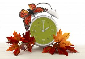 stock photo of time-saving  - Daylight Saving Time Ends concept with Autumn Fall theme retro style alarm clock on white wood background - JPG