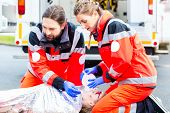 stock photo of accident emergency  - Emergency doctor and nurse or ambulance team giving oxygen to accident victim  - JPG