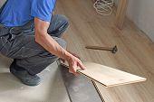 stock photo of laminate  - male carpenter puts the laminate in the room - JPG