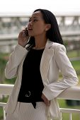 Business Woman With Cell Phone Looking Up poster