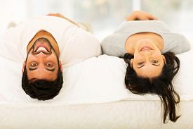 image of indian  - cheerful young indian couple lying on bed looking at the camera - JPG